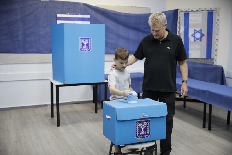 A man and his son vote at a polling station in Rosh Haayin, Israel, Tuesday, Sept. 17, 2019. Israelis began voting Tuesday in an unprecedented repeat election that will decide whether longtime Prime Minister Benjamin Netanyahu stays in power despite a looming indictment on corruption charges. (AP Photo/Sebastian Scheiner)