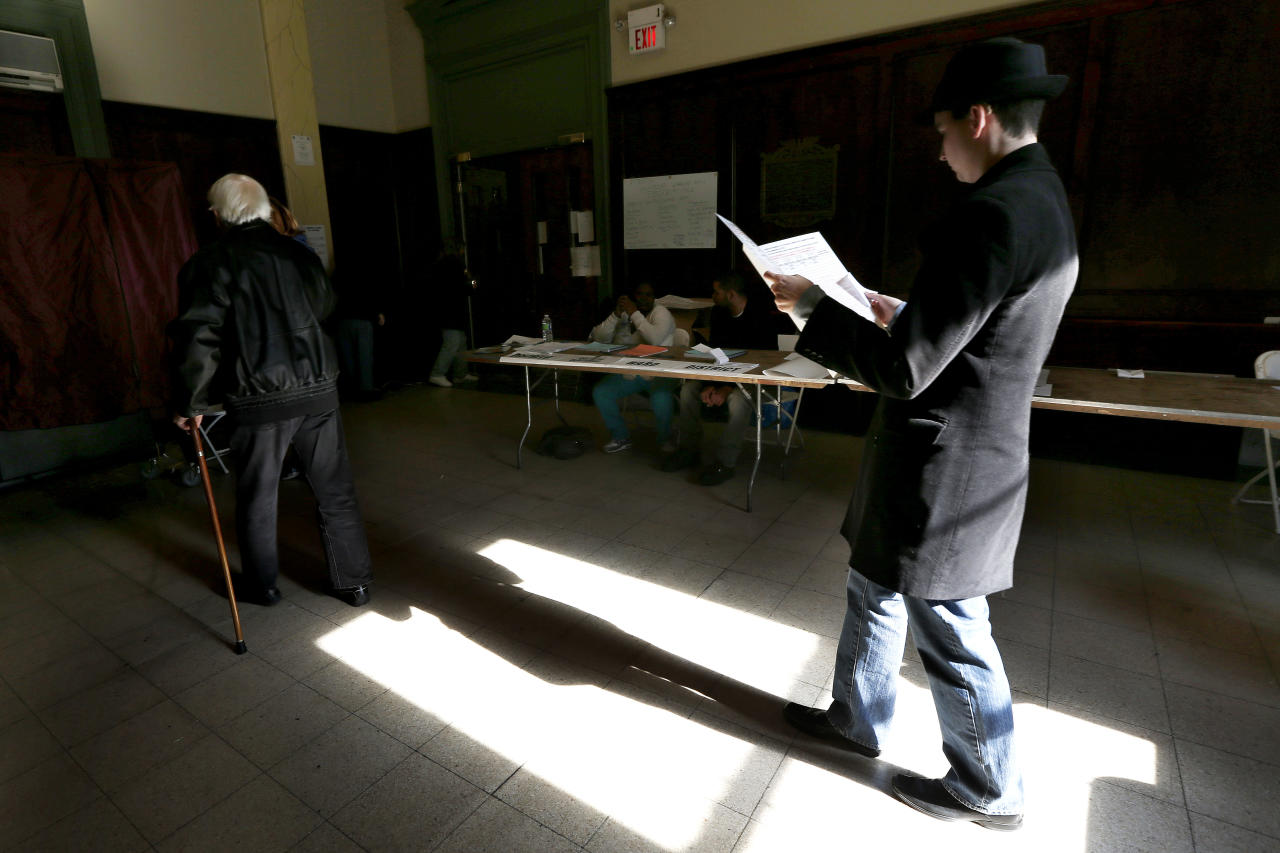 Sunlight shines on a man as he reads over a sample ballot while waiting in line to cast his vote at Hoboken City Hall on Election Day, Tuesday, Nov. 6, 2012, in Hoboken, N.J. Voting in the U.S. presidential election was the latest challenge for the hundreds of thousands of people in the New York-New Jersey area still affected by Superstorm Sandy, as they struggled to get to non-damaged polling places to cast their ballots in one of the tightest elections in recent history. (AP Photo/Julio Cortez)