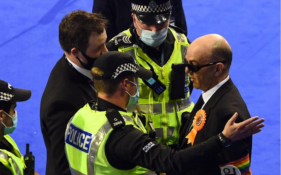 Police eject members of the Liberal Party, including their candidate Derek Jackson during counting the votes of the Scottish elections at the Emirates in Glasgow - ANDY BUCHANAN/AFP