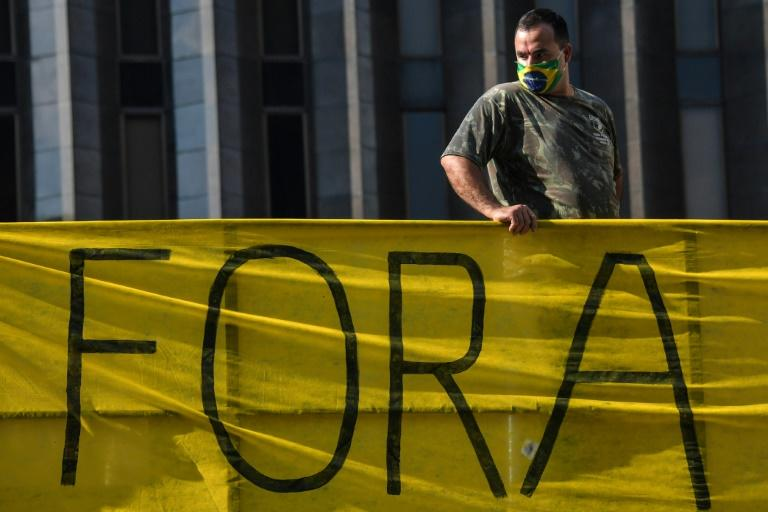 A supporter of Brazilian President Jair Bolsonaro wearing a face mask depicting the Brazilian flag is seen at a demonstration against quarantine and social distancing measures imposed in Sao Paulo, Brazil, on May 1, 2020 (AFP Photo/NELSON ALMEIDA)