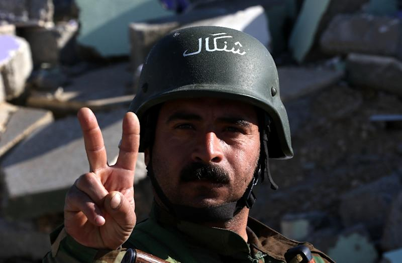 A Kurdish fighter flashes the victory sign in the northern Iraqi town of Sinjar, in the Nineveh Province, on November 13, 2015 (AFP Photo/Safin Hamed)
