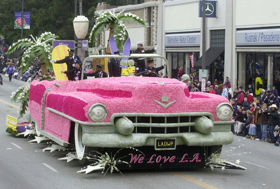 """New York City firefighter Bill Spade waves to the crowd from behind the wheel of a giant Cadillac decorated with pink carnations as the city of Los Angeles float, themed """"We Love LA,"""" makes its way down Colorado Boulevard during the 113th Rose Parade in Pasadena, California January 1, 2002. Spade is the sole survivor of twelve firefighters from his company who responded to the attack on the World Trade Center on September 11. REUTERS/Jim Ruymen JR/ME"""