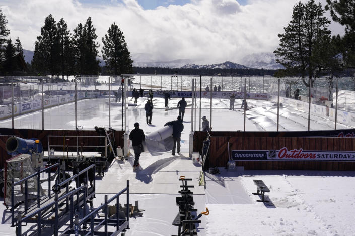 Workers put the finishing touches on the temporary ice rink, Friday, Feb. 19, 2021, built at the Edgewood Tahoe Resort, that will host two NHL games, this weekend at Stateline, Nev. The Colorado Avalanche will play the Vegas Golden Knights Saturday and the Philadelphia Flyers will face off against the Boston Bruins Sunday. (AP Photo/Rich Pedroncelli)