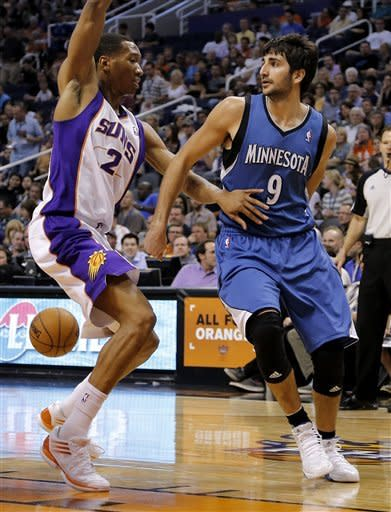 Minnesota Timberwolves' Ricky Rubio (9), of Spain, passes behind the back of Phoenix Suns' Wesley Johnson (2) during the first half of an NBA basketball game on Friday, March 22, 2013, in Phoenix. (AP Photo/Matt York)