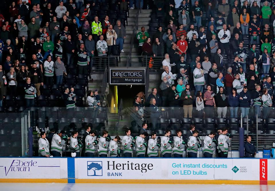 In this Jan. 9, 2018, photo, Seattle Thunderbirds hockey players join fans in standing during the singing of the national anthem at the ShoWare Center in Kent, Wash., about 20 miles south of Seattle. Hockey's history in Seattle dates back more than a century to when the Seattle Metropolitans hoisted the 1917 Stanley Cup.