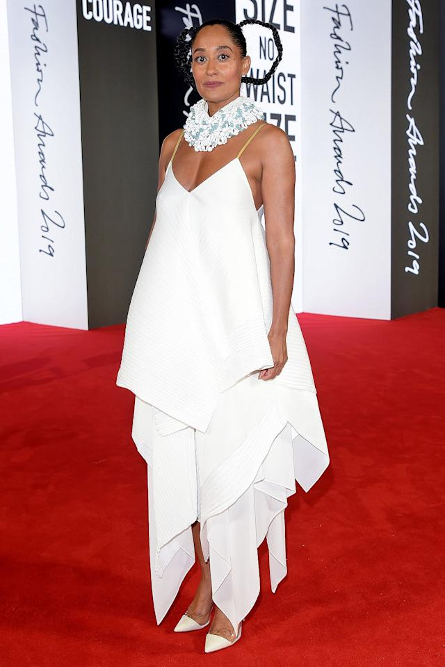 in a pleated and layered white gown by Loewe with ruffled collar, teamed with white pointed-toe pumps and whimsical looped-up braids in her hair.