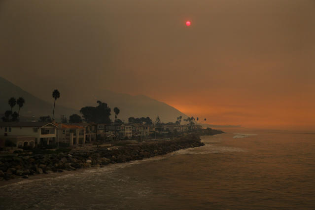 <p>Homes stand along the beach as the sun is visible through thick smoke from a wildfire Wednesday, Dec. 6, 2017, in Ventura, Calif. (Photo: Jae C. Hong/AP) </p>