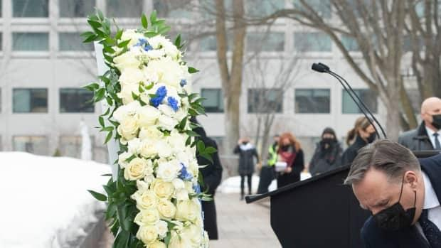 Premier François Legault and his wife, Isabelle Brais lay roses during a ceremony in Quebec City to mark one year since the World Health Organization declared COVID-19 a global pandemic. (Jacques Boissinot/The Canadian Press - image credit)