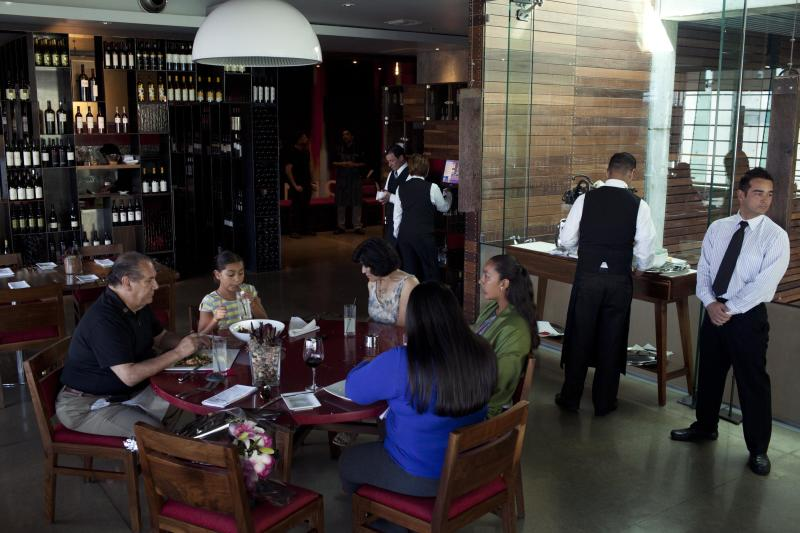 In this Sept. 27, 2012 photo, clients eat at Mission 19 restaurant in Tijuana, Mexico. A group of chefs are working to create a unique cuisine largely based on fresh seafood caught in the seas flanking Baja and the produce from its fertile valley. Mission 19 is part of this new culinary craze, known as Baja Med, which is a fusion of Mexican food with influences from the Mediterranean and Asia. (AP Photo/Alex Cossio)