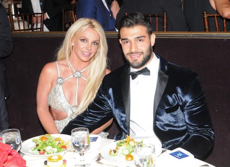 A woman in a silver dress sitting at a dinner table with a man in a blue velvet suit