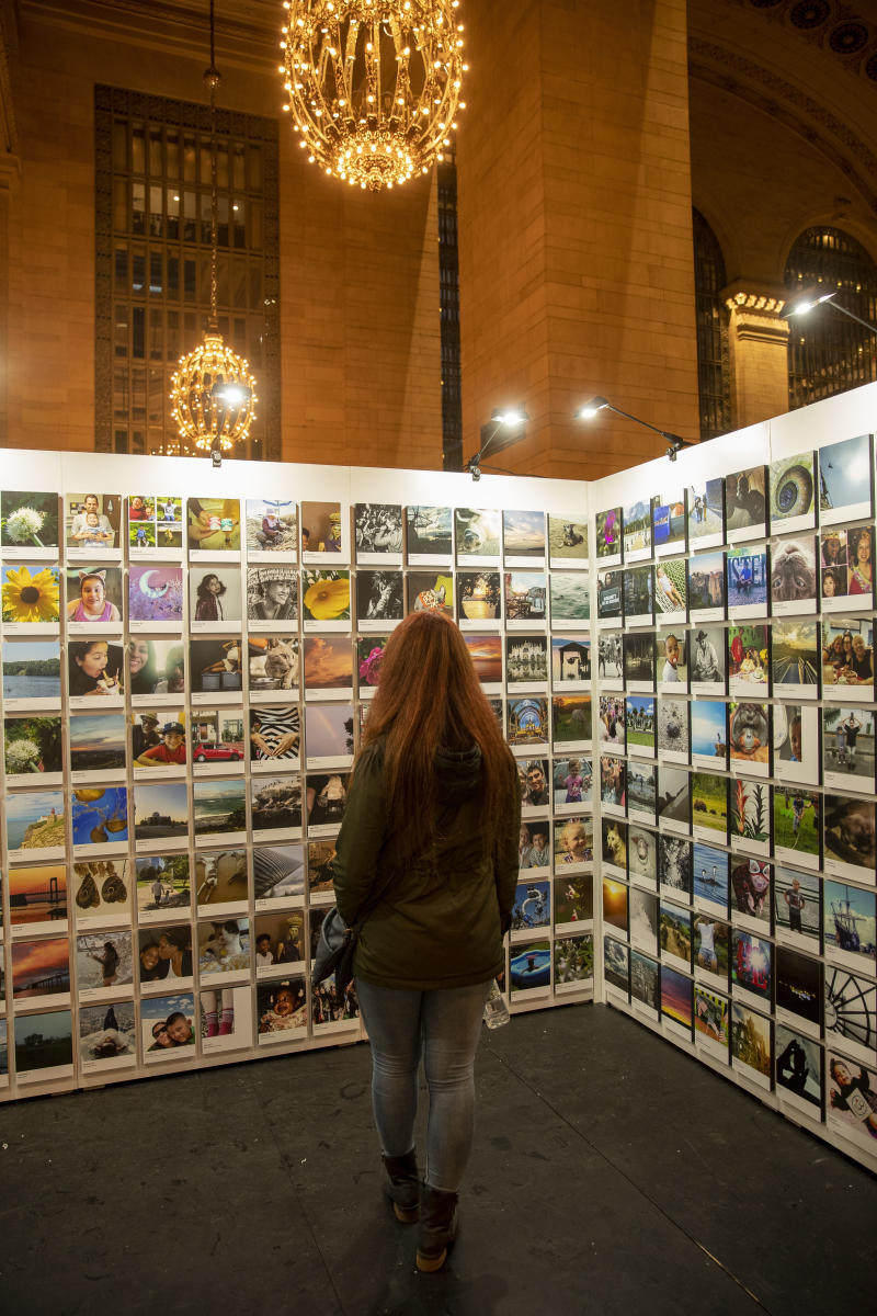A visitor checks out photos selected for the second annual Fujifilm Printlife exhibit. (Photo: Gordon Donovan/Yahoo News)