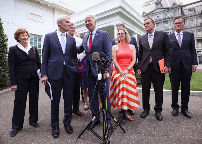 President Joe Biden (C), joined by from left to right, Sen Jeanne Shaheen (D-NH), Sen. Rob Portman (R-OH), Sen Bill Cassidy (R-LA), Sen. Kyrsten Sinema (D-AZ), Sen. Mark Warner (D-VA) and Sen Mitt Romney (R-UT), speaks after the bipartisan group of Senators reached a deal on an infrastructure package at the White House on June 24, 2021 in Washington, DC. Biden said both sides made compromises on the nearly $1 trillion infrastructure bill.