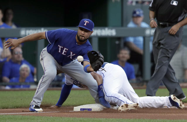 Kansas City Royals' Whit Merrifield, back, beats the throw to Texas Rangers third baseman Isiah Kiner-Falefa for a stolen base during the first inning of a baseball game at Kauffman Stadium in Kansas City, Mo., Tuesday, June 19, 2018. (AP Photo/Orlin Wagner)