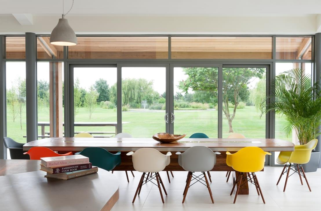 <p>We just had to highlight this image due to the fantastic way in which the colourful dining chairs (Scandinavian style, thank you) complement the fresh greens visible outside. And that elongated wooden table looks ripe and ready to host a magnificent feast with friends and family.</p>  Credits: homify / Dan Wray Photography