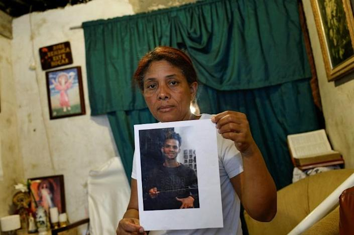 Carmen Arroyo, whose son Cristian was killed in September 2018, poses holding his picture at her home in the Petare slum, Caracas (AFP Photo/STR)