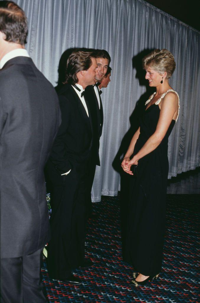 <p>The actor chatted with Princess Diana at the premiere of <em>Backdraft </em>in London in a classic tuxedo. The Princess wore a black sleeveless gown with beaded straps designed by Bellville Sassoon. </p>
