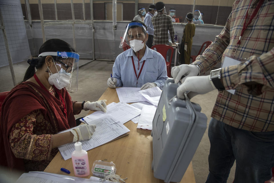 Election officials sit wearing masks and face shields during the counting of votes of Assam state assembly election in Gauhati, India, Sunday, May 2, 2021. With Indian hospitals struggling to secure a steady supply of oxygen, and more COVID-19 patients dying amid the shortages, a court in New Delhi said it would start punishing government officials for failing to deliver the life-saving items. (AP Photo/Anupam Nath)