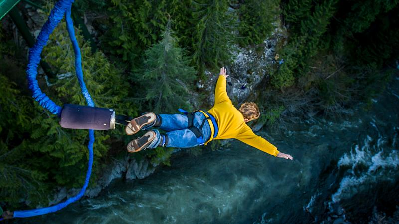 Young man bungee jumping over river.