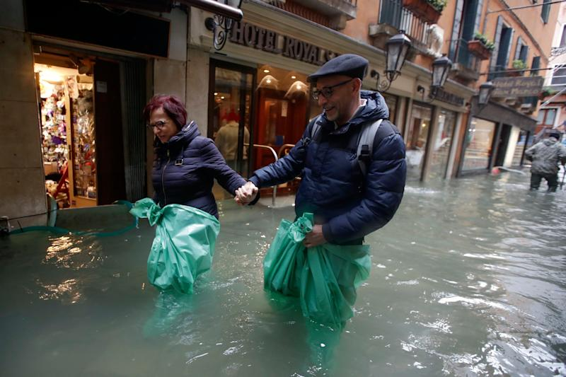 A couple wades their way through water in Venice, Italy, on Nov. 15, 2019.  (Photo: ASSOCIATED PRESS)