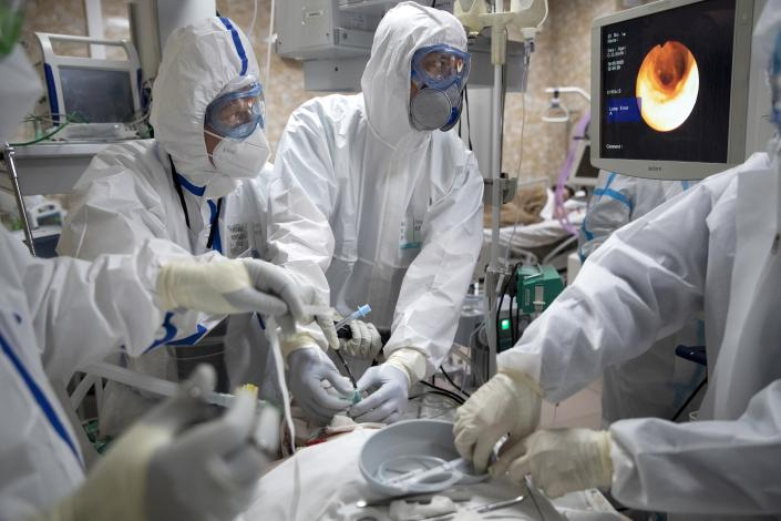 In this photo taken on Friday, May 15, 2020, Dr. Osman Osmanov, center, and Dr. Konstantin Glebov, center left, perform tracheal intubation on a coronavirus patient on artificial lung respiration at an intensive care unit of the Filatov City Clinical Hospital in Moscow, Russia. Moscow accounts for about half of all of Russia's coronavirus cases, a deluge that strains the city's hospitals and has forced Osmanov to to work every day for the past two months, sometimes for 24 hours in a row. (AP Photo/Pavel Golovkin)