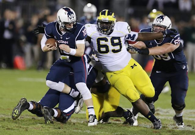 Michigan defensive tackle Willie Henry (69) chases down Connecticut quarterback Chandler Whitmer (10) during the second half of an NCAA college football game, Saturday, Sept. 21, 2013, in East Hartford, Conn. Michigan won 24-21. (AP Photo/Charles Krupa)