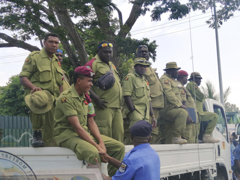 Security personnel on the back of a truck wait to be paid at Rita Flynn Netball Centre in Port Moresby, Papua New Guinea, Tuesday, Nov. 20, 2018.. Opposition lawmaker Bryan Kramer said disgruntled police and prison guards stormed Papua New Guinea's Parliament in a pay dispute that stemmed from an international summit hosted by the South Pacific island nation last weekend. (Jam Morales via AP)