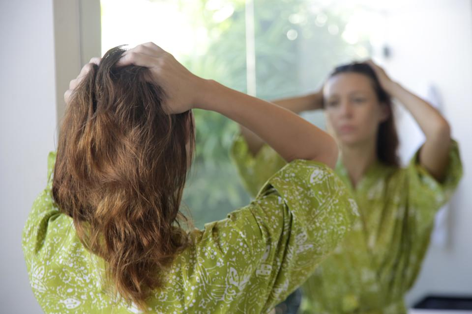 Young brunette applying hair oil with her fingers in the bathroom