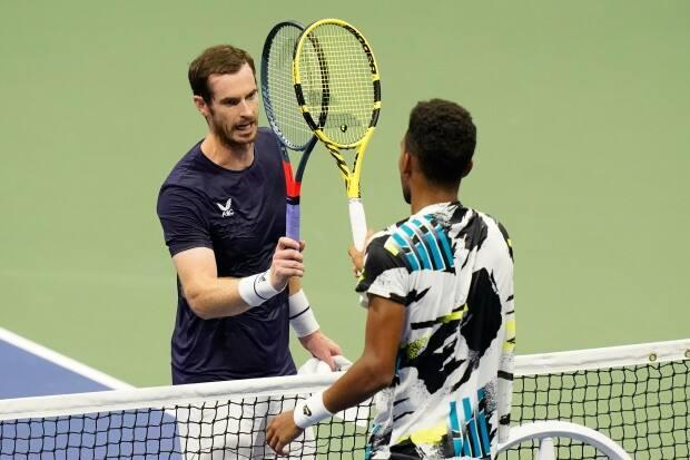 Felix Auger-Aliassime, of Canada, right, taps rackets with Andy Murray, of Great Britain, during the third round of the U.S. Open in 2020. The Canadian has drawn the two-time Olympic gold medallist in the first round of the Tokyo 2020 tournament. (Frank Franklin II/The Associated Press - image credit)