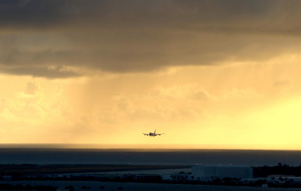 FILE - In this April 6, 2020 file photo, a plane lands as the sun sets over the Pacific Ocean in Honolulu. The small, tight-knit community of about 72,000 people on the neighboring Hawaiian island of Kauai spent the first seven months of the pandemic mostly COVID-free. Then in October, statewide travel restrictions eased and the island, which had only 61 known cases of coronavirus from March through September, went from zero cases in October to at least 84 new infections in just seven weeks. (AP Photo/Caleb Jones, File)