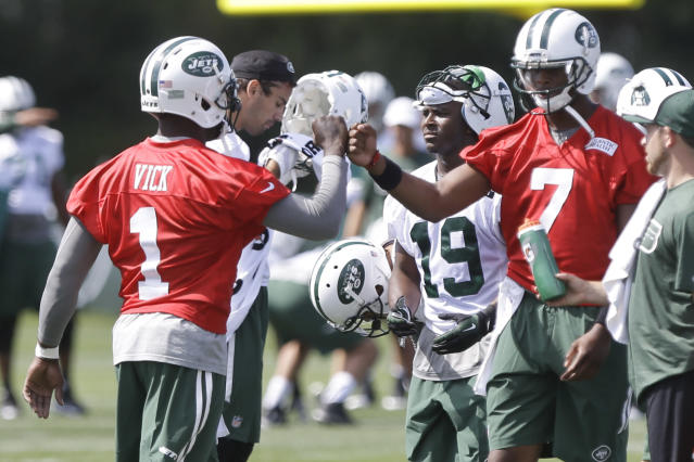 New York Jets quarterbacks Michael Vick (1) and Geno Smith (7) fist bump at the Jets NFL football training camp Thursday, July 24, 2014, in Cortland, N.Y. (AP Photo)
