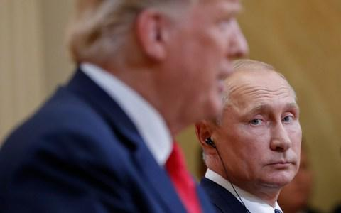 Russian President Vladimir Putin, right, looks over towards President Donald Trump, left, as Trump speaks during their joint news conference at the Presidential Palace in Helsinki - Credit: AP