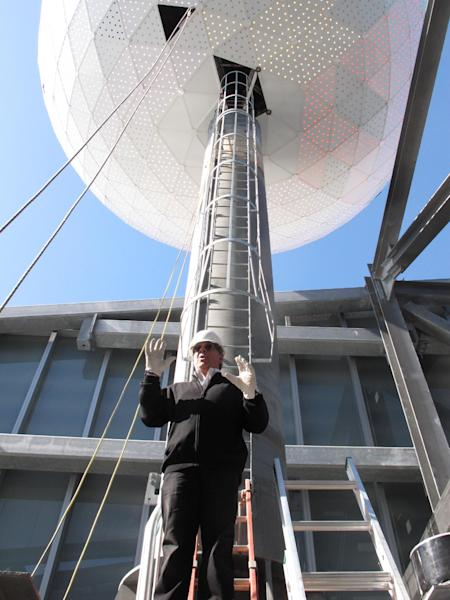 """Mitch Gorshin, who designed the iconic illuminated ball atop the Revel casino in Atlantic City, N.J., after climbing down out of the device on March 7, 2012. Gorshin, whose father Frank played """"The Riddler"""" on the """"Batman"""" TV series, says the ball is a constantly changing piece of artwork that will define the identity of the $2.4 billion resort, due to open on April 2. (AP Photo/Wayne Parry)"""
