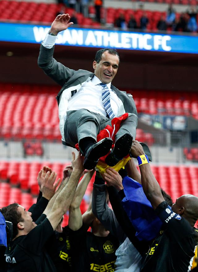 Wigan Athletic's manager Roberto Martinez celebrate their win against Manchester City with his players at the end of their English FA Cup final soccer match at Wembley Stadium, London, Saturday, May 11, 2013. (AP Photo/Matt Dunham)