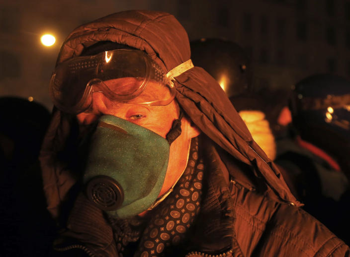 """A protester warms himself behind the barricade in central Kiev, Ukraine, early Friday Jan. 24, 2014. A top Ukrainian opposition leader on Thursday urged protesters to maintain a shaky cease-fire with police after at least two demonstrators were killed in clashes this week, but some in the crowd appeared defiant, jeering and chanting """"revolution"""" and """"shame."""" (AP Photo/Sergei Grits)"""
