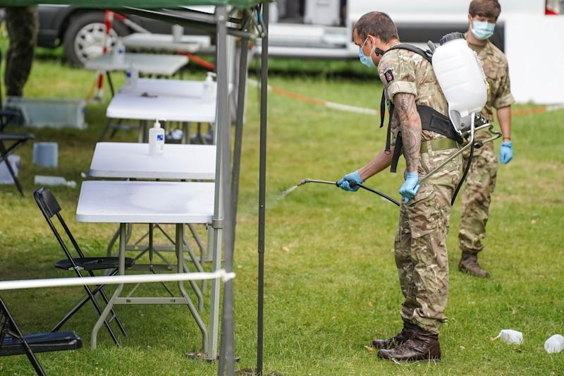 A member of the armed forces sprays disinfectant at a station set up for the testing for the novel coronavirus COVID-19, in Spinney Hill Park in Leicester, where several cases of the coronavirus have been detected. (Photo by Giannis Alexopoulos/NurPhoto via Getty Images)