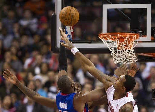 Toronto Raptors forward James Johnson, right, rejects Detroit Pistons forward Greg Monroe, left, during first-half NBA basketball game action in Toronto, Wednesday, Feb. 22, 2012. (AP Photo/The Canadian Press, Nathan Denette)