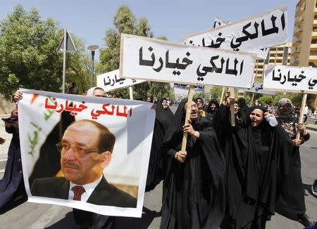People hold a portrait of Nuri al-Maliki and signs as they gather in support of him in Baghdad August 13, 2014. REUTERS/Ahmed Saad