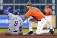 Houston Astros shortstop Carlos Correa (1) loses the ball between his legs before he attempts the tag on Texas Rangers' Isiah Kiner-Falefa (9) as he doubles during the seventh inning of a baseball game Friday, May 14, 2021, in Houston. (AP Photo/Michael Wyke)