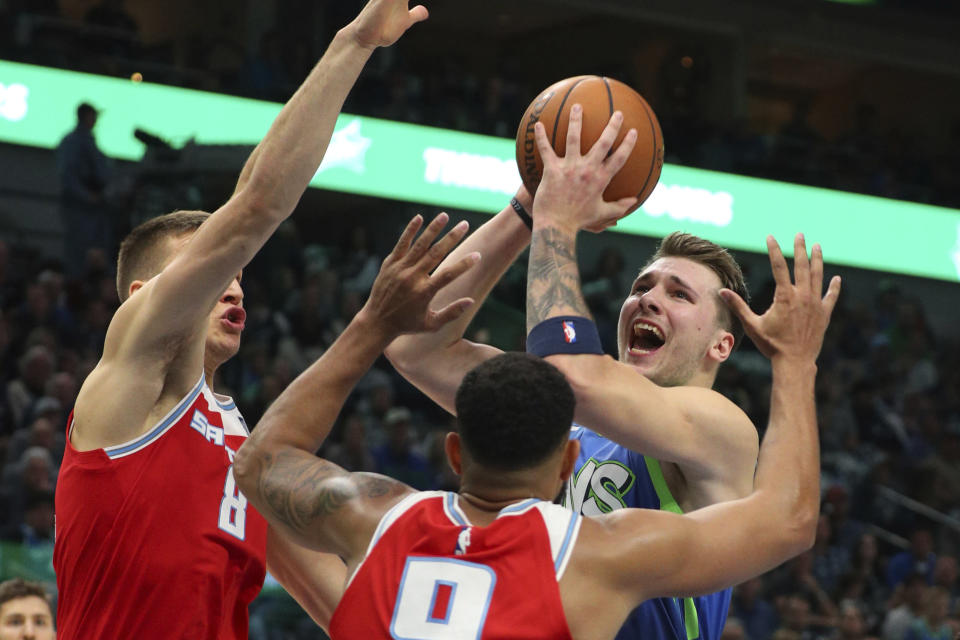 Sacramento Kings guard Bogdan Bogdanovic (8) and guard Cory Joseph (9) defend against a shot by Dallas Mavericks forward Luka Doncic (77) in the first half of an NBA basketball game Sunday, Dec. 8, 2019, in Dallas. (AP Photo/Richard W. Rodriguez)
