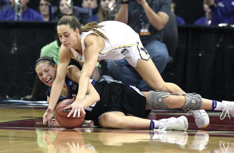 Kansas State guard Kayla Goth (10), bottom, battles Michigan guard Amy Dilk (1) for possession of the ball during the second half of a first-round game in the NCAA women's college basketball tournament in Louisville, Ky., Friday, March 22, 2019. (AP Photo/Timothy D. Easley)