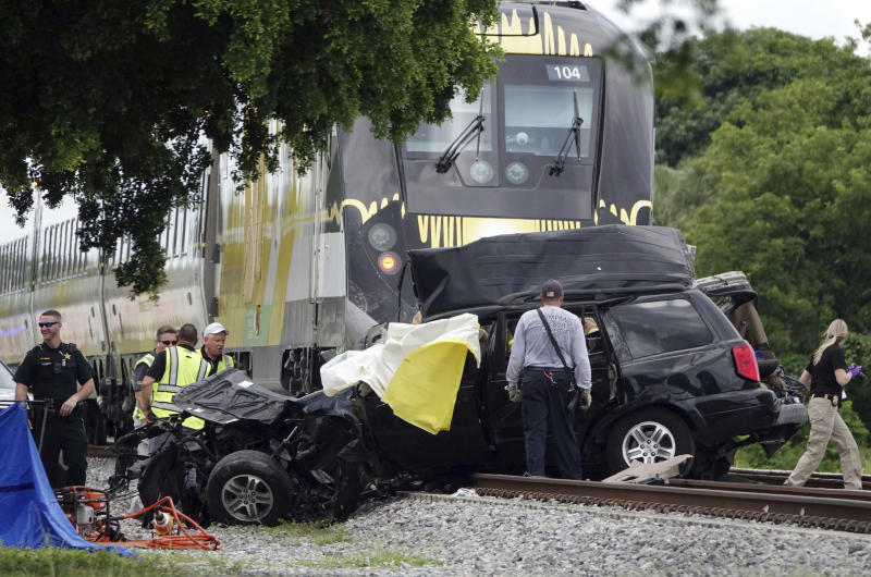 FILE - In this Aug 25, 2019 file photo, Broward Sheriff's Deputies and Pompano Beach Fire Rescue work the scene of a fatal accident on North Dixie Highway in Pompano Beach, Fla.  The Florida higher-speed passenger train service tied to Richard Branson's Virgin Group has the worst per-mile death rate in the U.S. The first death involving a Brightline train happened in July 2017 during test runs. An Associated Press analysis of Federal Railroad Administration data shows that since then, 40 more have been killed. That amounts to a rate of more than one a month and about one for every 29,000 miles (47,000 kilometers) the trains have traveled since the first death. (Joe Cavaretta/South Florida Sun-Sentinel via AP)