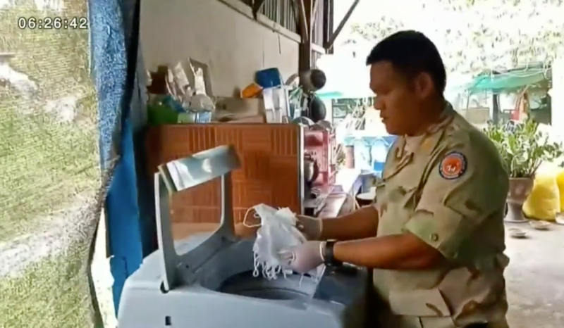 A Thai police officer pulls a handful of masks from a washing machine.