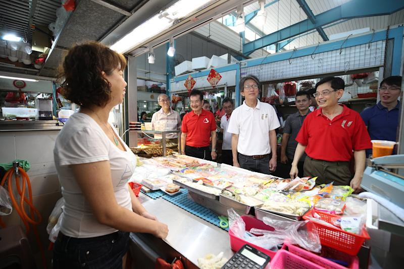 Singapore Deputy Prime Minister Heng Swee Keat (second from right) speaks with hawkers at East Coast GRC during a walkabout in July 2019. To his right is former minister Lim Swee Say, who is retiring from politics and stepping down as MP for East Coast. (PHOTO: Heng Swee Keat/Facebook)