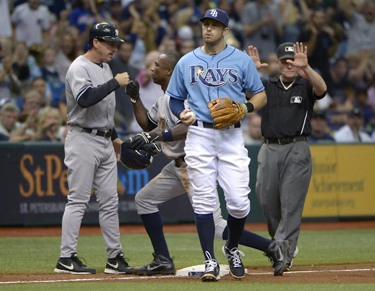 Tampa Bay Rays third baseman Evan Longoria, front, walks toward the mound as New York Yankees' Alfonso Soriano, second from left, is congratulated by coach Rob Thomson, left, after Soriano stole third base during the 11th inning of a baseball game in St. Petersburg, Fla., Sunday, Aug. 25, 2013. The Yankees won 3-2.(AP Photo/Phelan M. Ebenhack)