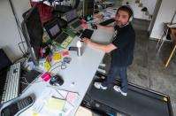Belgian Yves Hanoulle, IT professional, walks on a treadmill as he works in his home in Ghent
