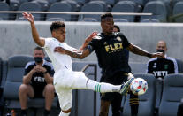 Austin FC midfielder Daniel Pereira Gil, left, and Los Angeles FC midfielder Mark-Anthony Kaye (14) vie for the ball during the first half of an MLS soccer match Saturday, April 17, 2021, in Los Angeles. (AP Photo/Ringo H.W. Chiu)