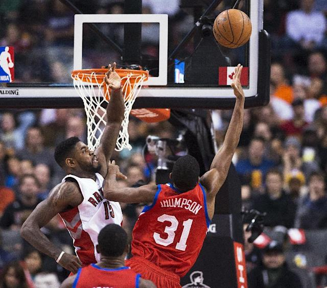 Toronto Raptors' Amir Johnson, left, defends at the net against Philadelphia 76ers' Hollis Thompson during the first half of an NBA basketball game in Toronto on Friday, Dec. 13, 2013. (AP Photo/The Canadian Press, Aaron Vincent Elkaim)