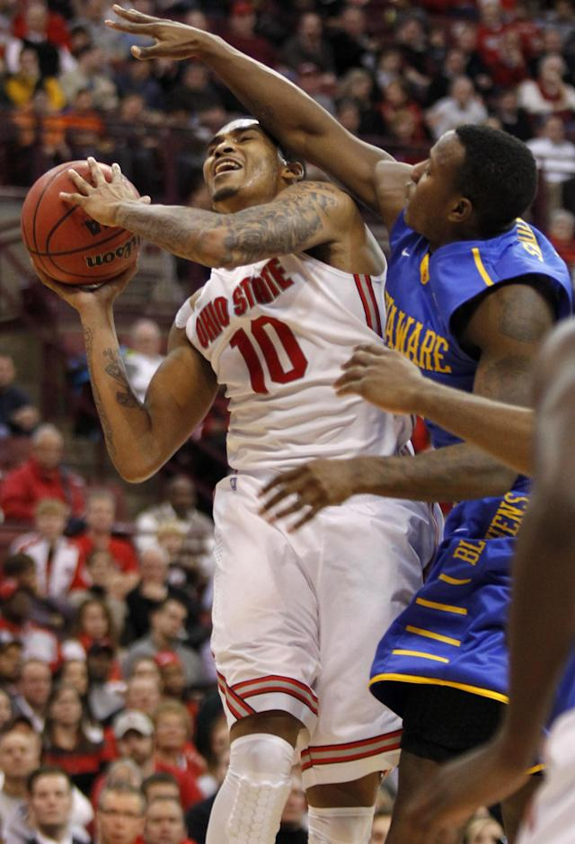 Ohio State's LaQuinton Ross, left, goes up to shoot against Delaware's Devon Saddler during the second half of an NCAA college basketball game in Columbus, Ohio, Wednesday, Dec. 18, 2013. Ohio State won 76-64. ( AP Photo/Paul Vernon)