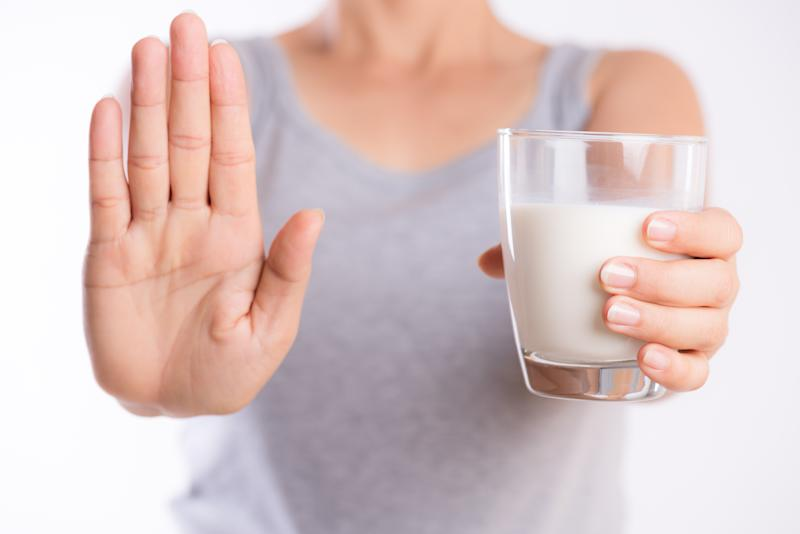 Woman hand holding glass of milk while putting her other hand up saying stop.