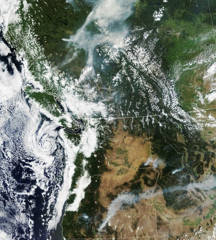 This NASA Earth Observatory satellite image obtained July 18, 2021 shows smoke soaring hundreds of miles from wildfires in the US and Canadian Northwest